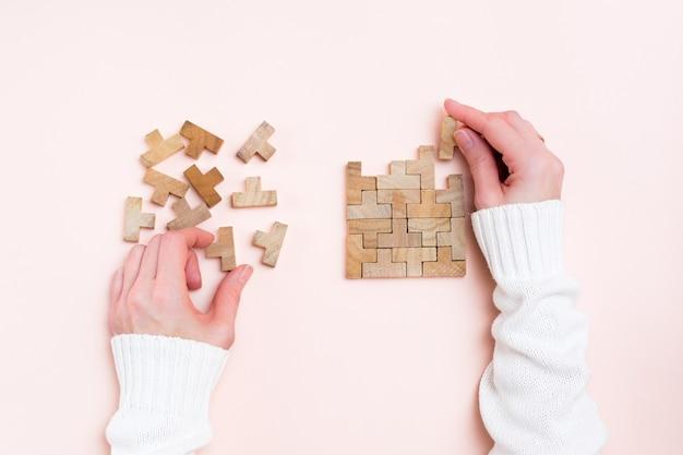 Organizacja i porządek. kobiece ręce układają drewniane puzzle na różowym tle.