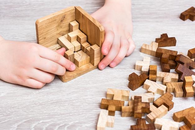 Organizacja i porządek. ręce dzieci składają drewniane elementy układanki w składaną formę