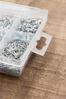Organizer do paznokci. różne rozmiary gwoździ ułożone w plastikowym pudełku.