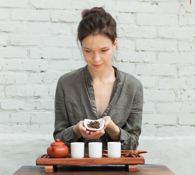 Oriental master ceremonii parzenia herbaty z białym murem na tle.