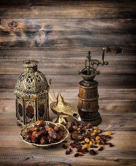 Orientalna latarnia i młyn. rodzynki i daty na drewnianym tle. sztuka martwa. retro stonowany obraz z winietą
