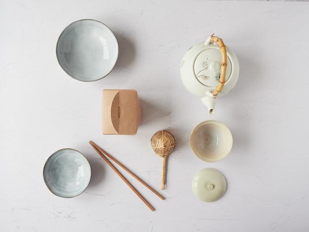 Orientalna zastawa stołowa. japoński i chiński czajnik, miski, pałeczki, bambusowe sitko i kartonowe opakowanie. widok z góry