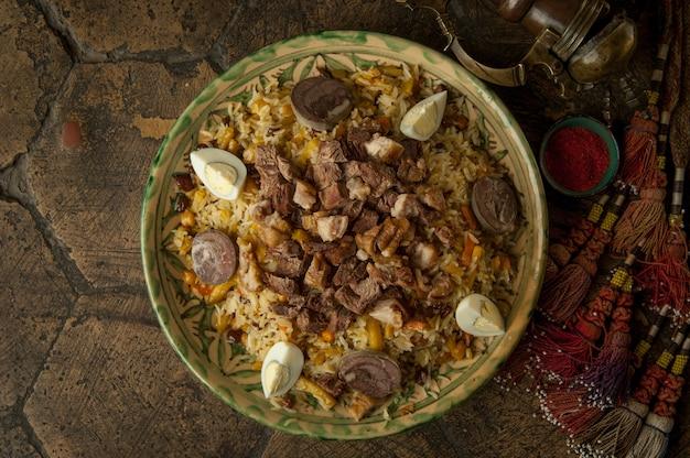 Orientalne dania na ozdobnych starych kafelkach. pilaw i dzban na ozdobnych starych kostkach brukowych