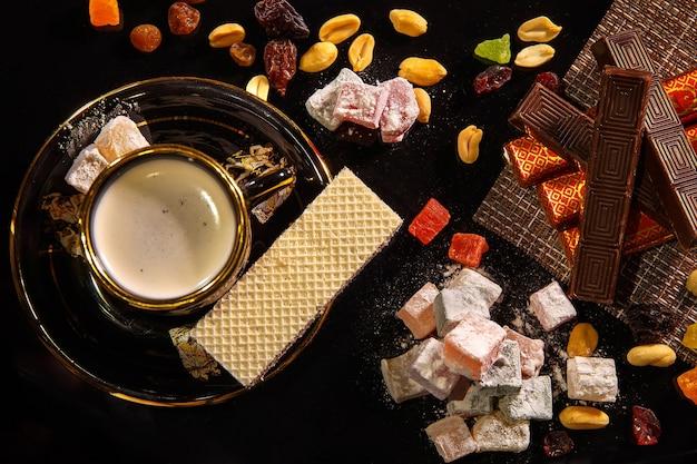 Orientalne słodycze natyutmort i filiżanka gorącej kawy na czarnym tle.
