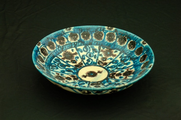 Orientalny antyczny talerz ceramiczny na czarnym tle zbliżenie
