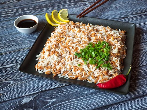 Orientalny pilaw ryżowy z orzo w talerzu na stole z ciemnego drewna. widok z góry.