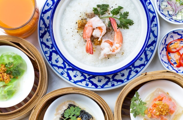 Orientalny zestaw śniadaniowy z congee i zestawem dim sum.