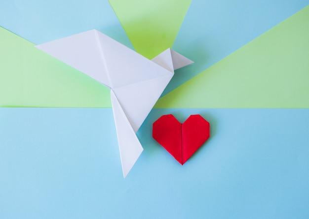 Origami biała gołębica i czerwone serce z zielonym i niebieskim tle geometrycznym