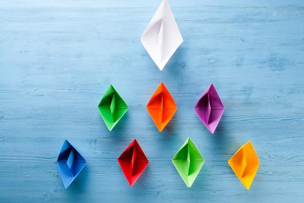 Origami papierowe łodzie na błękitnym stole