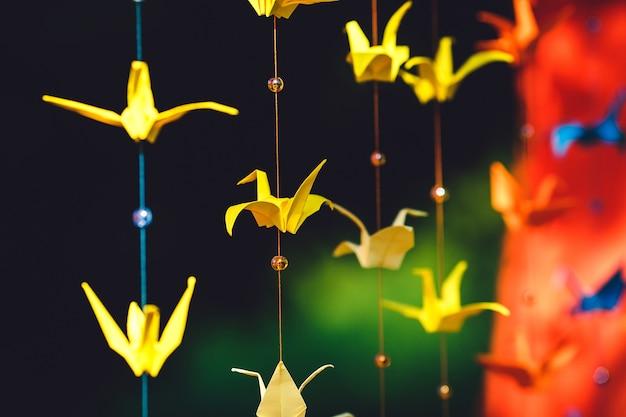 Origami z kolorowego papieru w postaci żurawi zawieszonych na sznurku. ślubny wystrój z kolorowego papieru.