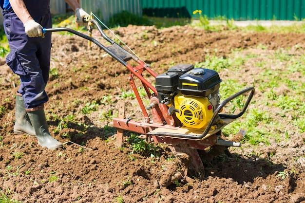 Orka w ogrodzie kultywatorem. prace rolnicze przy orce pola do siewu nasion. mężczyzna orze ziemię kultywatorem silnikowym.