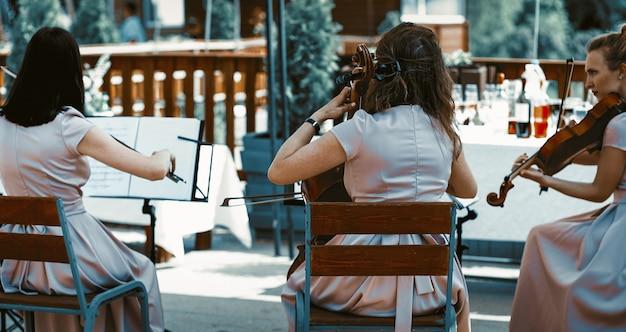 Orkiestra smyczkowa występująca na letnim tarasie