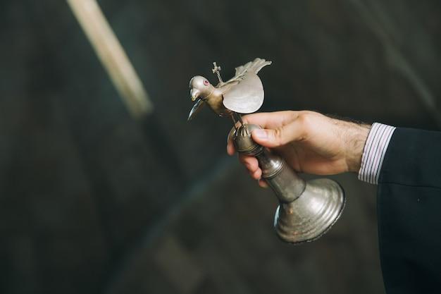 Ormiański ksiądz w klasztorze trzymający srebrnego ptaka podczas rytuału chrztu