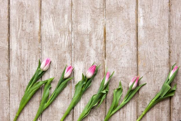 Ornament różowe tulipany na drewnianym tle. płynie na drewnie z copyspace. ślub, prezent, urodziny, 8 marca, koncepcja kartki z życzeniami na dzień matki