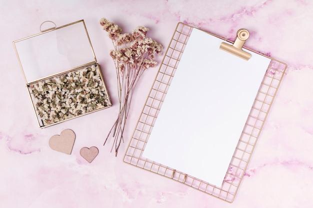 Ornamentuje serca blisko kwitnie w pudełku, roślinach i papierze ,.