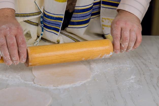 Ortodoksyjni żydzi rozwałkowują ciasto na mace na paschę i wkładają do pieca