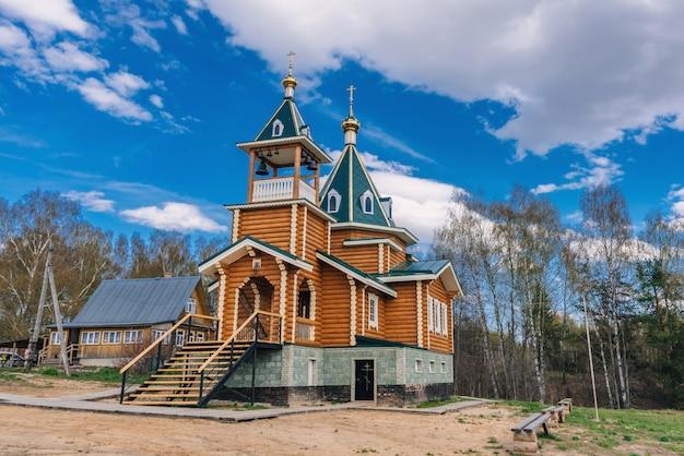 Ortodoksyjny chrześcijański nowożytny drewniany kościół w wiosce w rosja na letnim dniu
