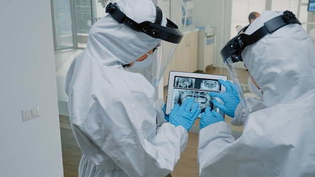 Ortodonci w klinice dentystycznej trzymają cyfrowy tablet z