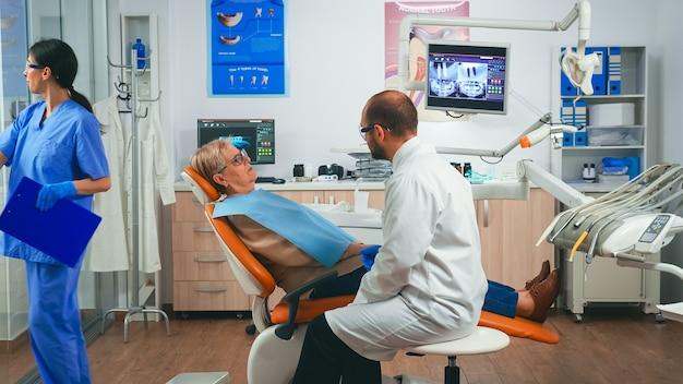 Ortodonta omawia badanie rezonansu magnetycznego z pacjentem siedzącym na fotelu stomatologicznym w klinice stomatologicznej. starsza kobieta wyjaśnia lekarzowi problem stomatologiczny, wskazując usta, podczas gdy pielęgniarka pracuje w tle