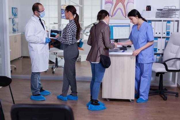 Ortodonta za pomocą tabletu wyjaśniający prześwietlenie zębów pacjentowi stojącemu w poczekalni gabinetu stomatologicznego