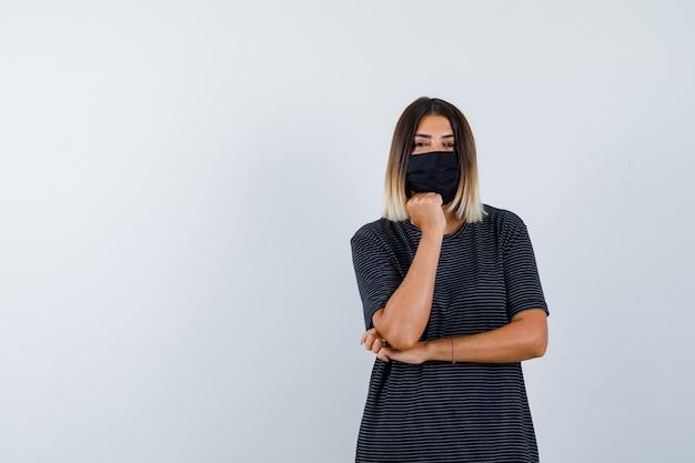Ortrait kobiety podpierającej brodę na pięści w czarnej sukience, masce medycznej i wyglądającej rozsądnie z przodu
