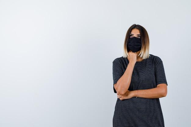 Ortrait kobiety podpierającej brodę na pięści w czarnej sukience, masce medycznej i zamyślonym widoku z przodu