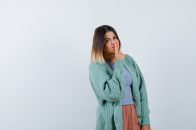 Ortrait kobiety pokazującej gest ciszy w zwykłym ubraniu i wyglądającej rozsądnie z przodu