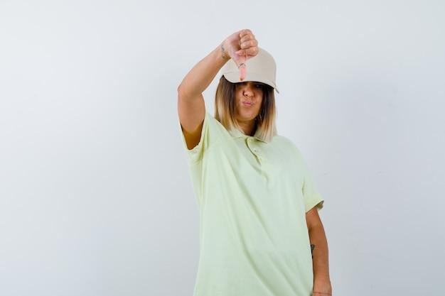 Ortrait młodej damy pokazujący kciuk w dół w koszulce, czapce i niezadowolony widok z przodu