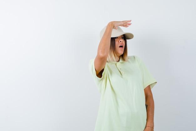 Ortrait młodej damy trzymającej dłoń na głowie, aby wyraźnie widzieć w t-shircie, czapce i patrząc zdziwionym widokiem z przodu