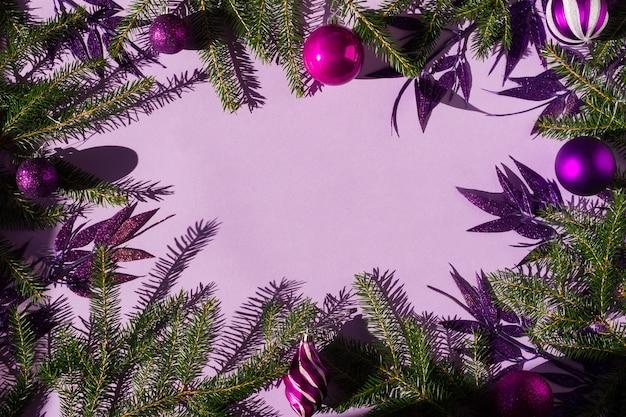 Oryginalne świąteczne liliowe tło z zielonymi gałązkami świerkowymi, fioletowymi kulkami i ozdobnymi liśćmi z brokatem. kopię przestrzeni.