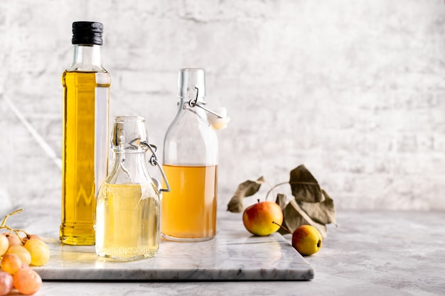 Oryginalne szklane butelki z różnymi rodzajami octu na marmurowym stole przy stole z białej cegły. skopiuj miejsce. poziomy.