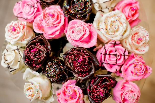 Oryginalny bukiet białych, różowych i czekoladowych róż ozdobiony cukrem pudrem