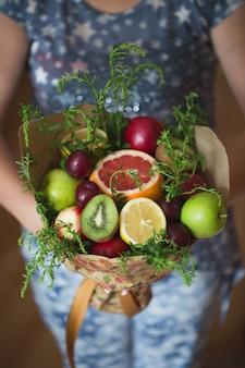 Oryginalny niezwykły jadalny bukiet warzyw i owoców w rękach dziewczynki