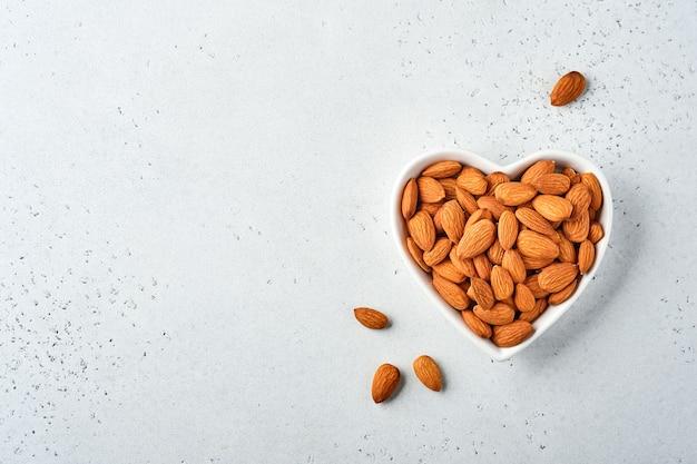 Orzech migdałowy w ceramicznej płytce w kształcie serca na białym tle. przekąska wegańskie jedzenie bez cukru.