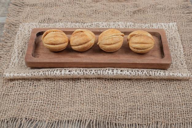 Orzech w kształcie na drewnianej płycie z jutą.
