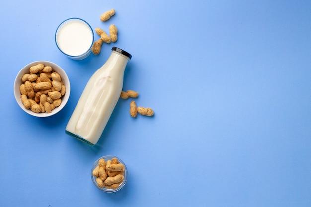 Orzechowe bezmleczne mleko w szklanej butelce z miską orzeszków ziemnych