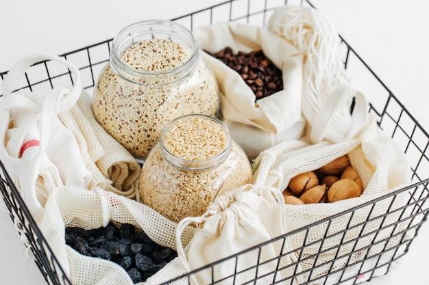 Orzechy, bakalie i kasze w eko-bawełnianych woreczkach i szklanych słojach w czarnym metalowym koszu. zakupy żywności bez marnotrawstwa. życie bez odpadów
