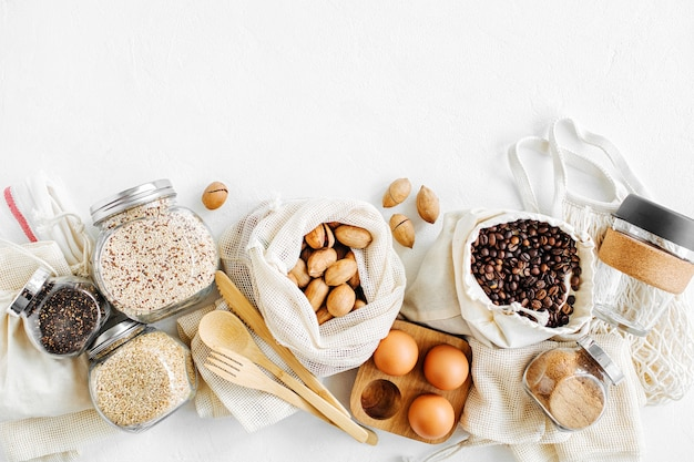 Orzechy, bakalie i kasze w ekologicznych bawełnianych torebkach i szklanych słoikach na białym stole w kuchni. zakupy żywności bez marnotrawstwa. życie bez odpadów