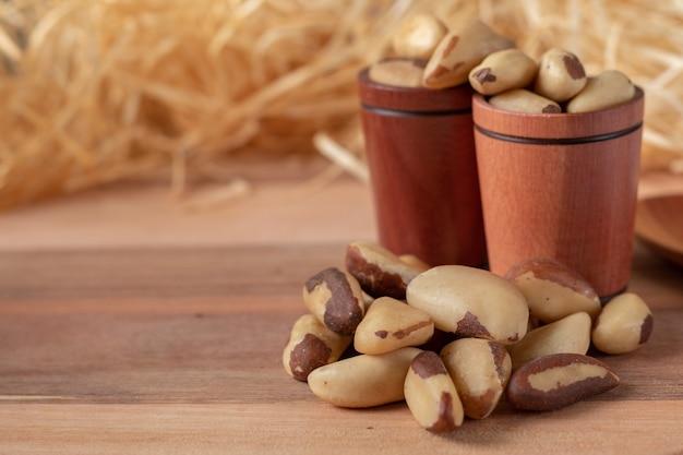 Orzechy brazylijskie na drewnianym stole iw drewnianych kubkach z tłem słomy. (castanha do brasil ou castanha do para)