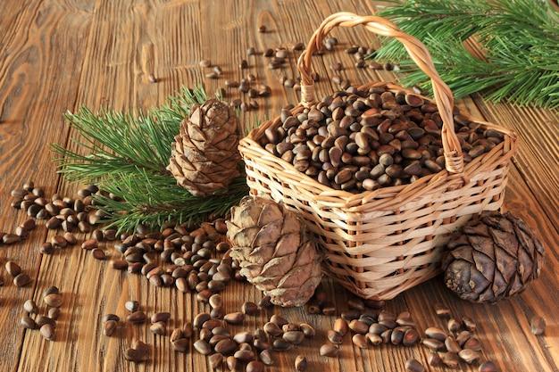 Orzechy cedrowe i szyszki cedrowe w wiklinowym koszu na drewnianym stole