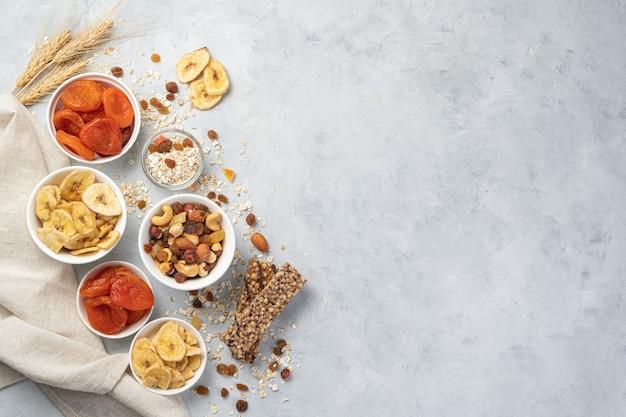 Orzechy, chipsy bananowe, suszone morele, rodzynki i batonik muesli na szarej ścianie z miejscem do kopiowania. zdrowe słodycze, energetyczna żywność witaminowa.