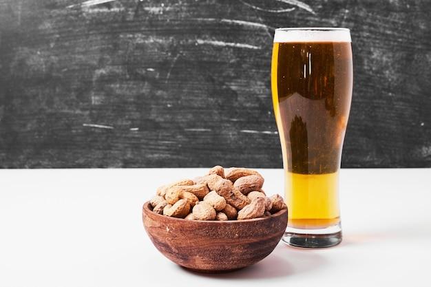 Orzechy i piwo na białym tle.