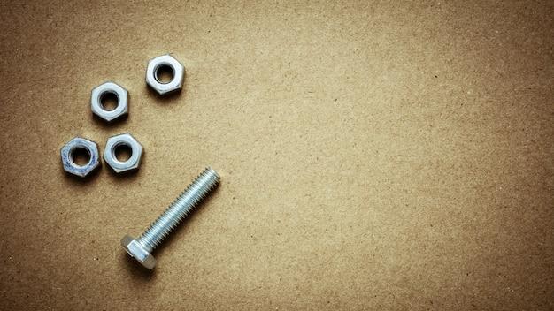 Orzechy i śruby na opuszczonym papierze. - dla tła koncepcji diy lub budowy.