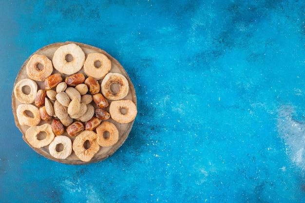 Orzechy i suszone owoce na desce, na niebieskim stole.