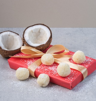 Orzechy kokosowe, kruche ciasto i pudełko prezentowe na marmurowym stole.