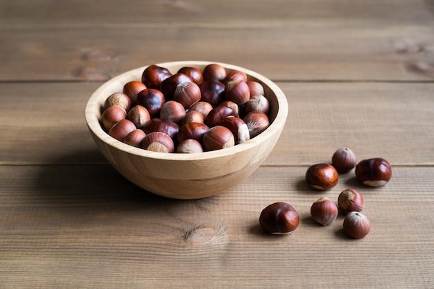 Orzechy laskowe i kasztany w drewnianej misce z bliska na drewnianym tle.