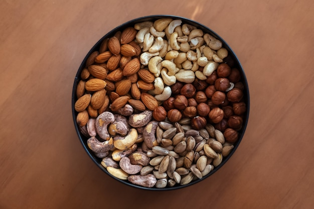 Orzechy laskowe, migdały, surowe orzechy nerkowca, smażone orzechy nerkowca i pistacje w talerzu na drewnianym stole.