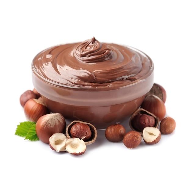 Orzechy laskowe rozłożone na szklanej płytce z orzechami na białym tle. pasta czekoladowa.