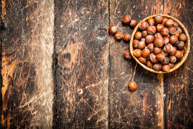 Orzechy laskowe w koszu. na drewnianym tle.