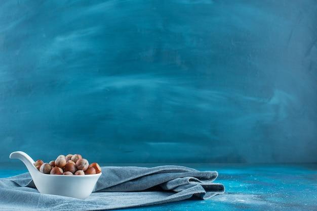 Orzechy laskowe w łyżce na kawałku tkaniny, na niebieskim stole.
